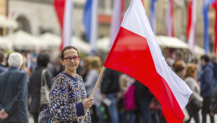 Woman on the street holding a flag of the Republic of Poland.